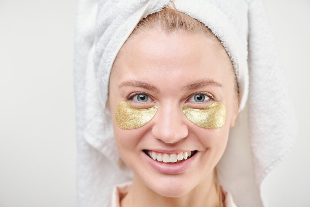 Cheerful girl with towel on head and revitalising golden under-eye patches